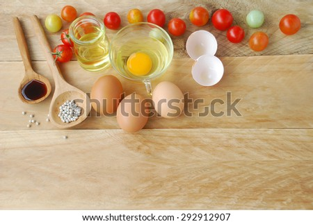 eggs and fresh tomatoes with vegetable oil in a glass container sauce and pepper seed in a ladle, placed on a wooden background in top view. - stock photo