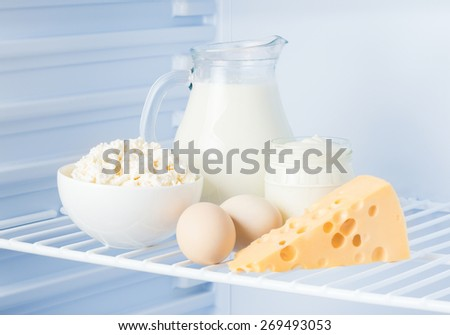 eggs and tasty healthy dairy products in the refrigerator: sour cream in the bank, cottage cheese in  bowl, eggs, cheese  and milk in a jar - stock photo