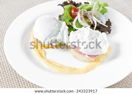 Eggs Benedict- toasted English muffins, ham, poached eggs, and delicious buttery hollandaise sauce for breakfast - stock photo