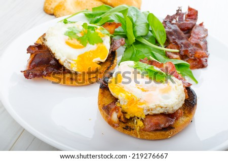 Eggs benedict with bacon and spinach on white plate - stock photo