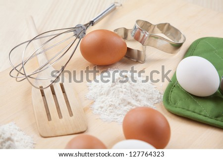 eggs, flour, cookie mold and whisk on wooden board together - stock photo