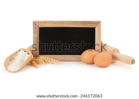 eggs, flour, wooden rolling pin and chalkboard - stock photo