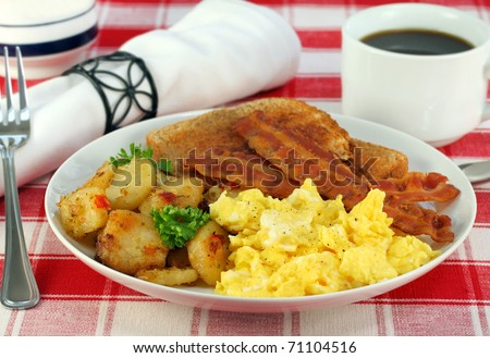 Eggs, home fries, bacon and toast for breakfast. - stock photo