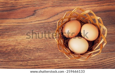 Eggs in a basket on wooden table - stock photo