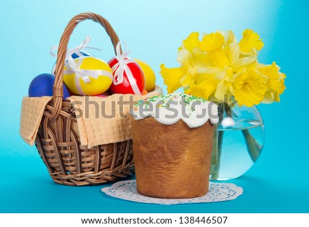 Eggs in a basket with a napkin, an Easter cake and a vase with narcissuses, on the blue - stock photo