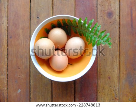 Eggs in a bowl on a wooden table. - stock photo