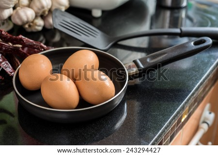 Eggs in a frying pan for breakfast - stock photo