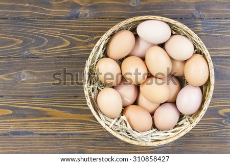 Eggs in bamboo basket on old wooden table - stock photo