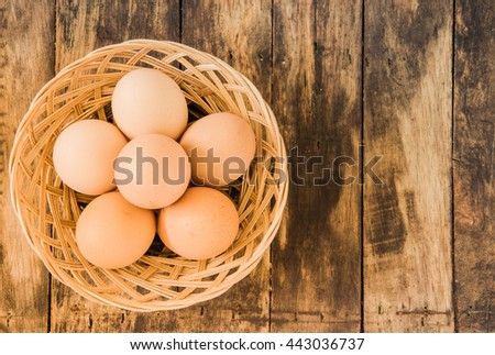 eggs in basket on old wooden background - stock photo