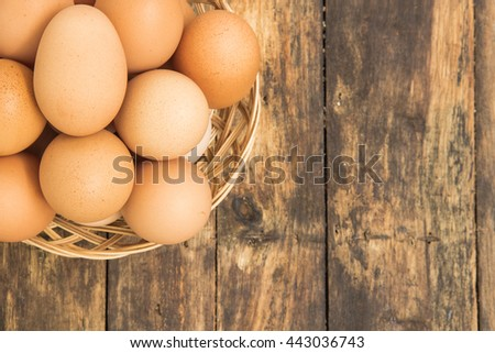 eggs in basket on old wooden background in natural lighting - stock photo