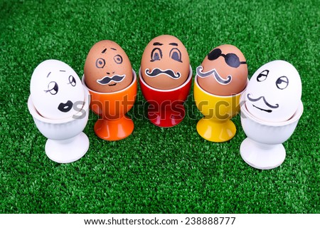 Eggs in egg cups on green background - stock photo
