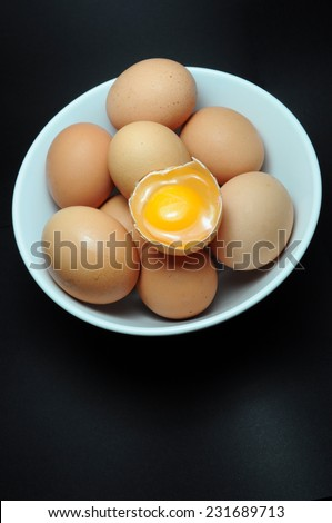 Eggs in plate with broken egg above - stock photo
