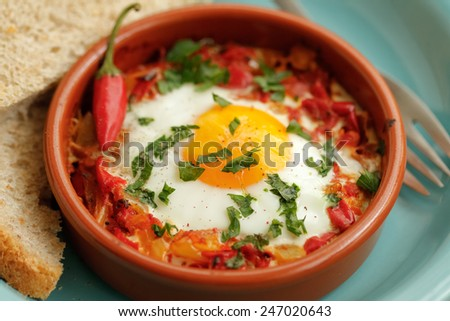 Eggs poached in tomato sauce and other vegetables served with bread. - stock photo