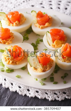 Eggs stuffed with salmon and cucumber closeup on a plate. vertical