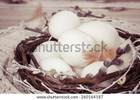 Eggs. White eggs in nest on a brown wooden table. Easter decoration. Done with vintage retro filter. A macro photograph with very shallow depth of field - stock photo