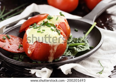 Eggs with mozzarella cheese baked in fresh tomatoes and garnished with chives. Extreme shallow depth of field. - stock photo