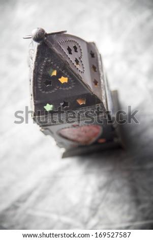 Egyptian fanous on grey textile - stock photo