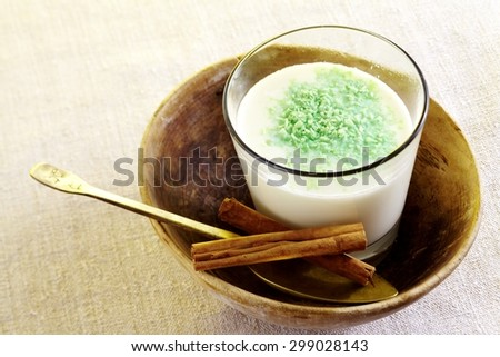 Egyptian Sahlab in cup on cloth close up with brass / metal spoon - stock photo