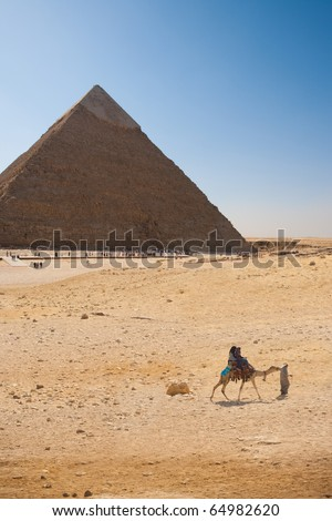 Egyptian tourists take a paid ride on a camel in front of the Pyramid of Khafre in Giza, Cairo, Egypt - stock photo