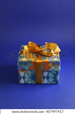 Eid festive gift. A closed gift box with islamic motif pattern and golden ribbon. - stock photo