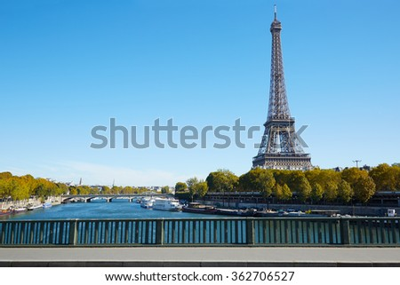 Eiffel tower and empty sidewalk bridge on Seine river in a clear sunny day, autumn in Paris - stock photo