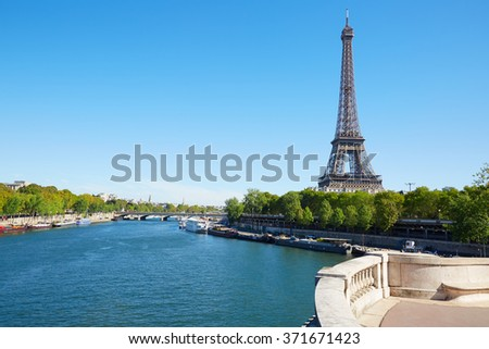 Eiffel tower and empty white balustrade on Seine river in a clear sunny day in Paris - stock photo