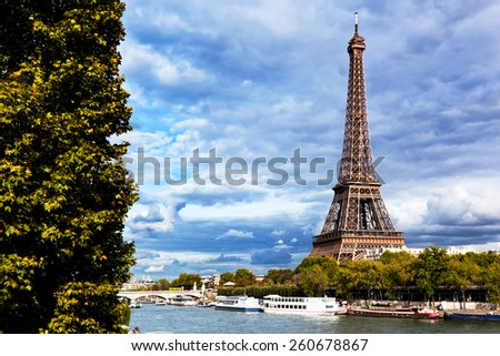 Eiffel Tower and Seine River, Paris, France. Unique perspective from behind trees next to tourist boats. - stock photo