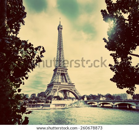 Eiffel Tower and Seine River, Paris, France. Unique perspective from behind trees next to tourist boats. Vintage - stock photo