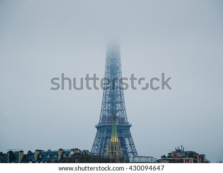 Eiffel tower disappearing in the mist at cloudy winter evening.  - stock photo