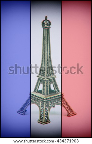 Eiffel Tower model on french flag. Dust and scratches applied for vintage analog effect - stock photo