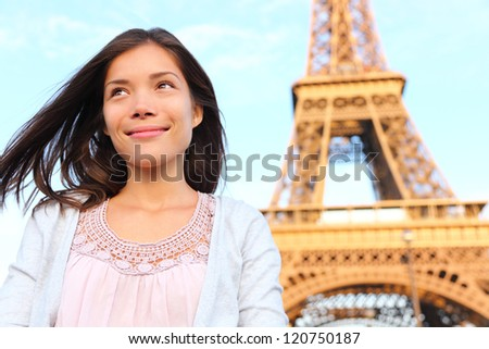 Eiffel tower Paris tourist woman smiling happy. Beautiful portrait of multiracial Asian Caucasian girl during travel in Europe. - stock photo