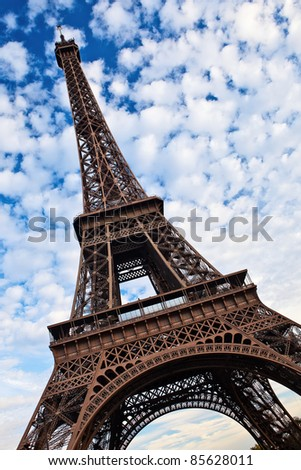 Eiffel tower tilted view over blue sky with white clouds. - stock photo