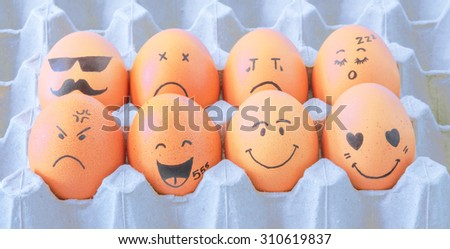 eight brown eggs  with faces drawn  arranged in carton - stock photo