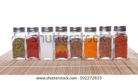 Eight jars of spices isolated over white - stock photo