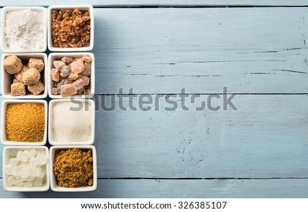 Eight kinds of sugar at left side of blue background top view - stock photo