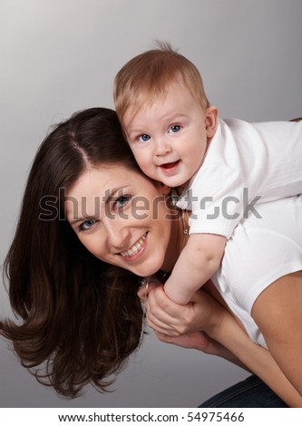 Eight-month baby is sitting on the back of mother. They look into lens. - stock photo