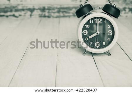 eight o clock, ratro white alarm clock on table - stock photo