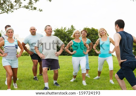 Eight people jogging in the park on a beautiful day - stock photo