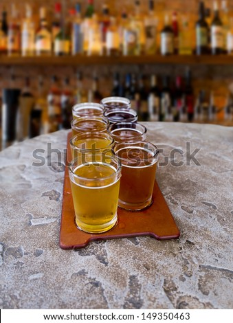 eight sampling glasses of beer on a serving paddle in a bar - stock photo