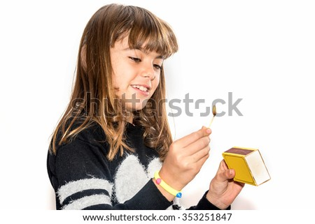 Eight year old girl playing with matches isolated on white.  Dangerous activity in the house. - stock photo