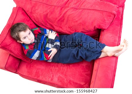 Eight years old boy expression mischievousness with arms closed on the couch by looking up in to your eyes, isolated on white - stock photo