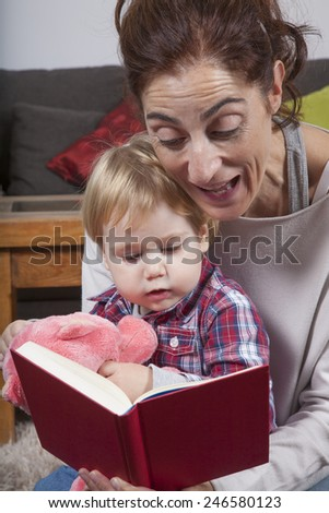 eighteen month aged blonde baby with brunette woman mother reading tale story red book indoor - stock photo