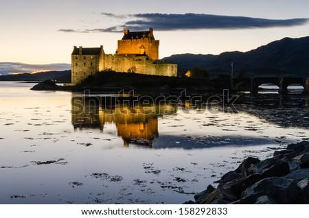 Eilean Donan castle at dusk / Eilean Donan the iconic Scottish castle at dusk - stock photo