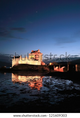 Eilean Donan Castle reflecting on Loch Duich at nightfall, as the Planet Jupiter begins to set in the night sky. - stock photo