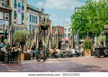 Eindhoven, Netherlands - May 24, 2015: People sitting at outdoors restaurant in the main square of Eindhoven. It is popular touristic place, with plenty of restaurants, bars, stores and clubs  - stock photo