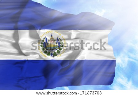 El Salvador waving flag against blue sky with sunrays - stock photo