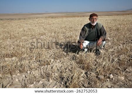 ELAZIG, TURKEY - JULY 3: Old farmer at drought field on July 3, 2008 in Elazig, Turkey. - stock photo