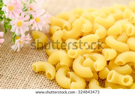Elbow macaroni noodles with flower on sack background. - stock photo