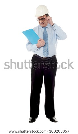 Elder architect posing in style as  he look at his business document - stock photo