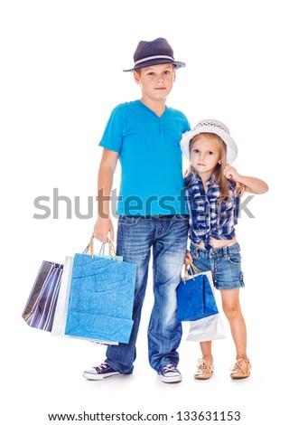 Elder boy and preschool girl in denim wear with customer paper bags - stock photo